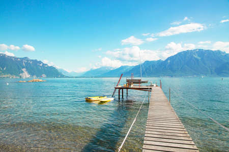 Lake view With a long bridge walkway for swimming and mountains In the summertime in Europe, traveling for a holiday with family