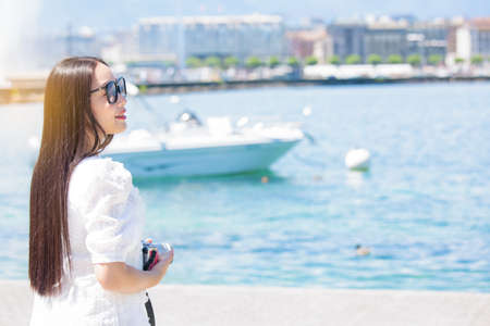 Asian beautiful woman is travel for holiday in the summer of Europe and taking a camera view landscape of lake and bright sky in Geneva Switzerland, copy space.