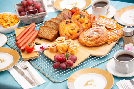 Breakfast Served in the morning with cereal bread, raisin bread, banana bread, sausage bread, chicken sausage, Natural corn flake breakfast cereal in cups and fruit on the breakfast table every day
