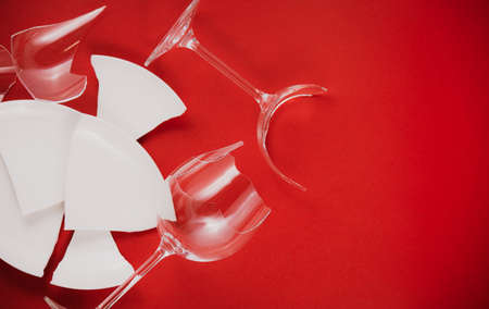 Broken Plate or broken water glass on the on the red background The concept of accidents in the kitchen is dangerous for the body and young children inside the house.