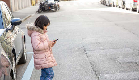 The young girl is watching the phone all day in the house or using a mobile phone for a long time hurts her eyes and has an aggressive atmosphere. Concept danger for children's mobile phone...