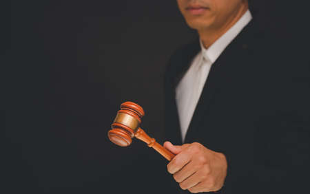Businessmen are holding an old judge's hammer to use for judgment and justice in a black background.