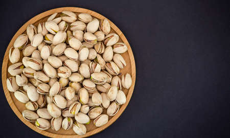 Peanuts Nut mixed salt in a wooden plate is Protein food and healthy food for diet food on a black background.