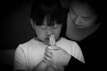 Asian face woman and child praying and worship to GOD Using hands to pray in religious beliefs and worship christian in the church or in general locations in While and Black background