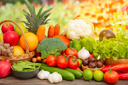 Group vegetables and Fruits Apples, grapes, oranges, pineapples, bananas in a wooden basket with carrots, tomatoes, guava, chili, eggplant, golden pod, green salad on wooden table in nature background