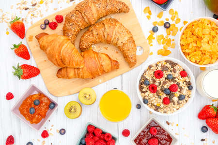 Breakfast Served in the morning with Butter croissant and corn flakes Whole grains and raisins with milk in cups and Strawberry, Blueberry, Raspberry, Kiwi, Fresh Orange Juice on the breakfast table. Stock Photo