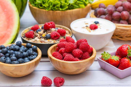 Group Fruits mixed and vegetables with salad bowl, nuts bowl, strawberry, banana, and pineapple, orange juice, vitamin c in food nature for health and diet in the top view on the wood table. Imagens