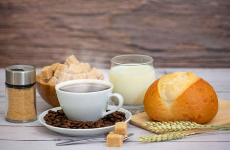 Breakfast in the morning with black coffee cup with bread with Croissant and fruit on the wooden table. Stock Photo
