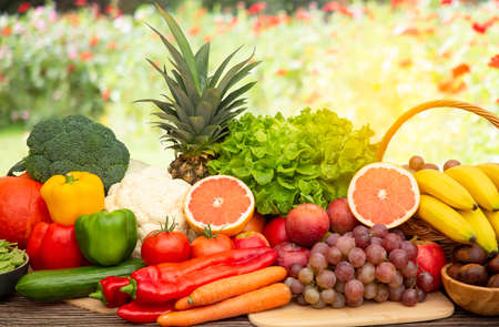 Group vegetables and Fruits Apples, grapes, oranges, and bananas in the wooden basket with carrots, tomatoes, guava, chili, eggplant, and salad on the table.Healthy food concept Stock Photo