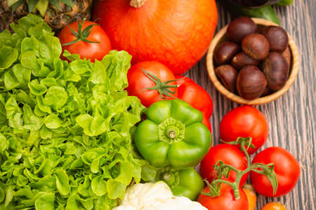 Group vegetables and Fruits Apples, grapes, oranges, and bananas in the wooden basket with carrots, tomatoes, guava, chili, eggplant, and salad on the table.Healthy food concept
