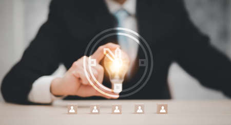 Businessman hand holding light bulb with icon on wood cube and working on desk, Creativity and innovation are keys to success.Concept of new idea and innovation with Brain and light bulbs, working a
