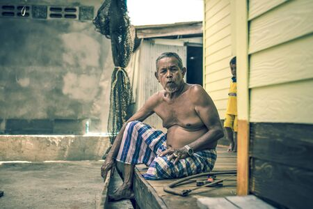 phangnga: The old man was repairing his wooden bed,  [Panyee Island, Phang-nga, Thailand  5-Apr-2015]