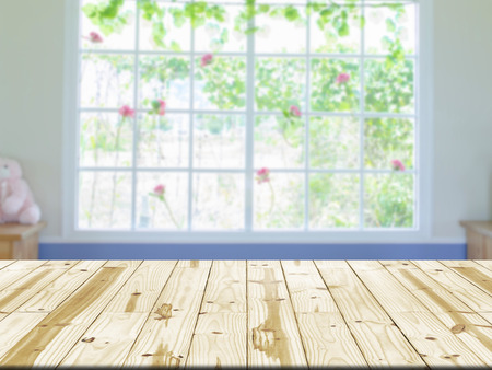 window display: Wood table top on window interior room blurry background. Stock Photo