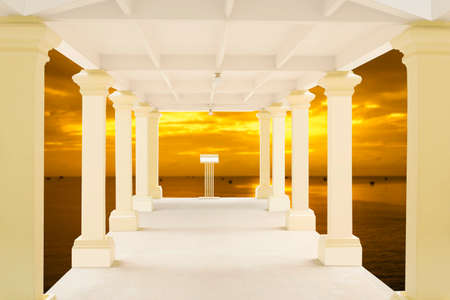 straight path: Walkway in tunnel structure and blurry sunset over the sea in background Stock Photo