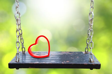 light chains: Red heart shape on old wooden swing and green blurred backgrounds.