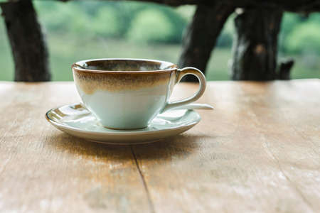 vapour: Soft focus on cup of coffee on wood table