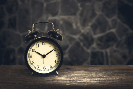 clockwise: Alarm clock on wood with blurry stone walls in background. Concept of time.