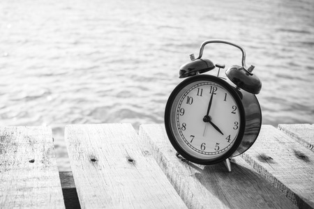 pm: Alarm clock on wood and blurry sea in background. 4 pm. black and white. Stock Photo