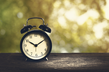 Alarm clock on wood with blurry shinny bokeh in background Concept of time.