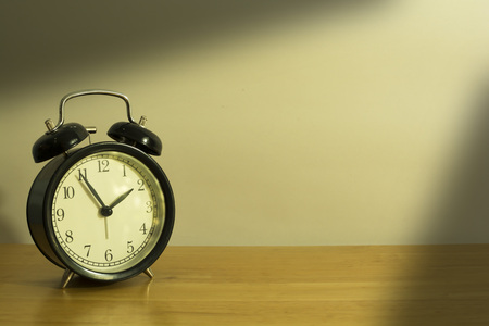 Alarm clock on wood table. Time concept.