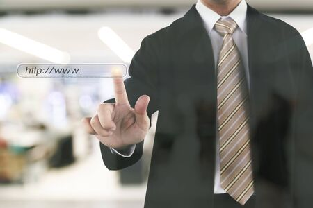 Businessman hand touching on web site to shopping. Blurry shopping mall in background. Stock Photo