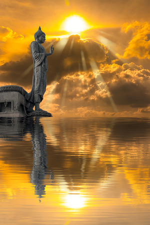 Buddha statue against on Golden sky with sunlight and water reflection. Abstract Religion. 版權商用圖片