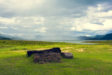 Abstract beautiful nature. Tree stump on forground and mountain with rainy on background. landscape shot at Kaemg Krachan National Park.