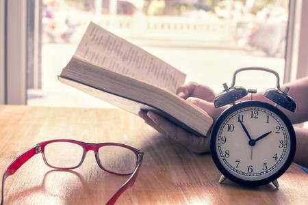 テーブルの上の本を読む。レトロな目覚まし時計に焦点を当てます。コンセプトを読む時間。