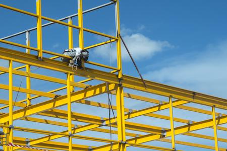 Pracownik jest spawaniem stali na budowie.