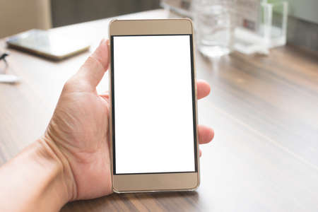 Hand holding smartphone with white screen on wood table in restaurant.