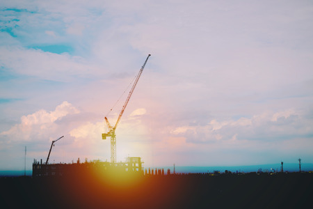 Silhouette of crane at construct site. Construction background Stock Photo