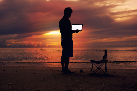 A man holding laptop with white screen on the beach and sunset scene.