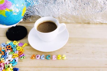 Coffee cup and alphabet on wood table with wording SUCCESS.