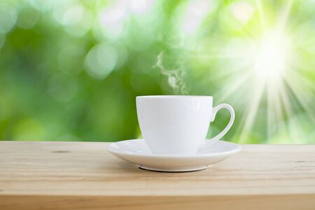 Cup of hot coffee on table and green bokeh white sunlight background. Stock Photo