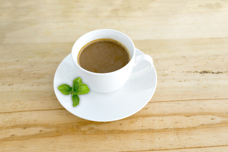A Cup of hot coffee on table with Mint leaves.