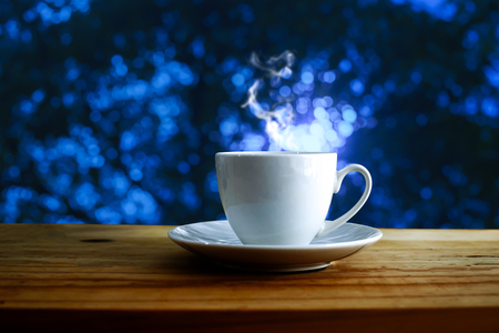 Cup of hot coffee on table and blue bokeh background.