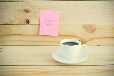 Cup of hot coffee on table and paper note Love DAD on wood wall.