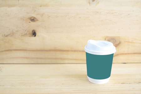 Cup of coffee on wood background.