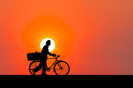 Silhouette image. A man walking with bicycle.