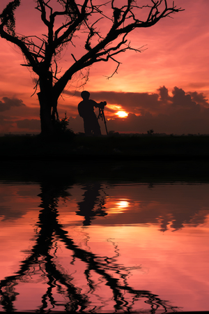 Silhouette image. Shadow of photographer near by death tree with sunset. Stock Photo