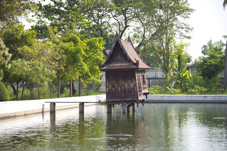 Old wooden house in the pond at Wat Yai Suwannaram, Phetchaburi, Thailand. It was an old library for the collection of buddhist scriptures. Stock Photo