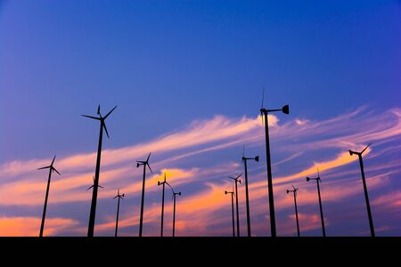 Silhouette image of Wind turbine with Colorful sky background.