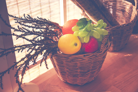 Soft focus on Artificial Fruits in a basket on wood table. Home decoration