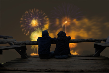 Couple relaxing on wooden terrace and looking to fireworks on the sky. Stock Photo