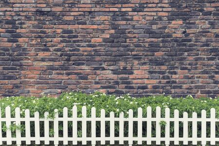 White fence decorated with green trees and old brick walls in background. Stock Photo