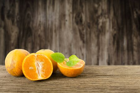Stack of Orange fruit on old wooden plate. Stock Photo