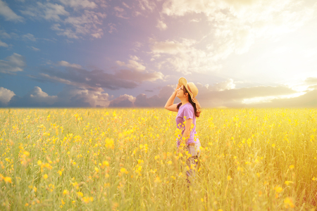 Happy asian woman standing and looing to sky in the yellow field