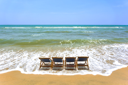 Summer background. 4 chairs on the beach. Stock Photo