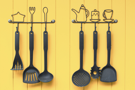 Collection of ladles hanging on the yellow walls.