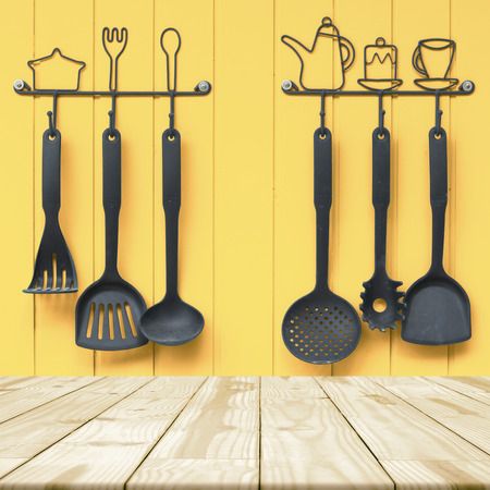 Empty wooden table for display product and Collection of ladles in background.
